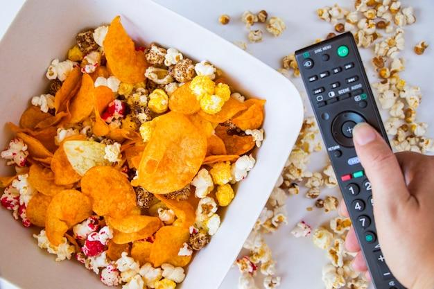 Popcorn fritto e patatine in una ciotola sullo sfondo bianco, mano che tiene il controller tv, vista ad angolo basso
