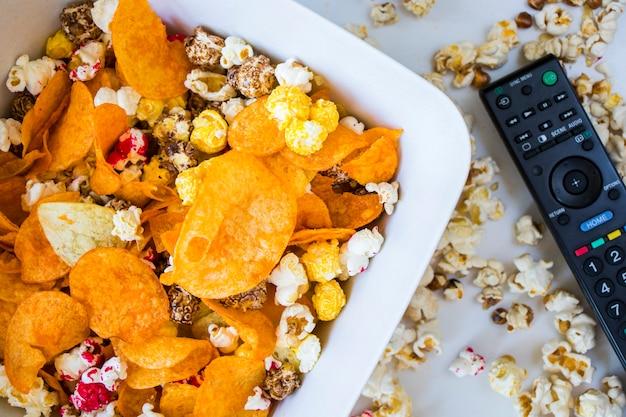 Popcorn fritto e patatine in una ciotola su sfondo bianco e controller tv, vista ad angolo basso