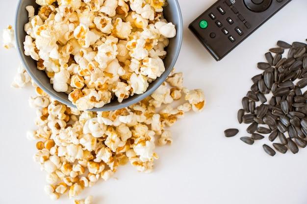 Popcorn fritti su sfondo bianco e controller tv