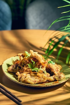 Maiale fritto in pastella con carote e cetrioli con salsa agrodolce. cucina cinese