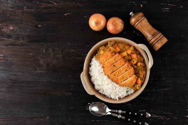 Maiale fritto, manzo o cotoletta di pollo al curry con riso - stile alimentare giapponese. vista dall'alto su piatto in ceramica tavolo in legno nero con dadi di patate e carote, spazio per copiare il testo