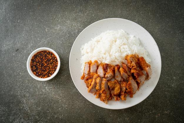 Maiale fritto ricoperto di riso con salsa piccante