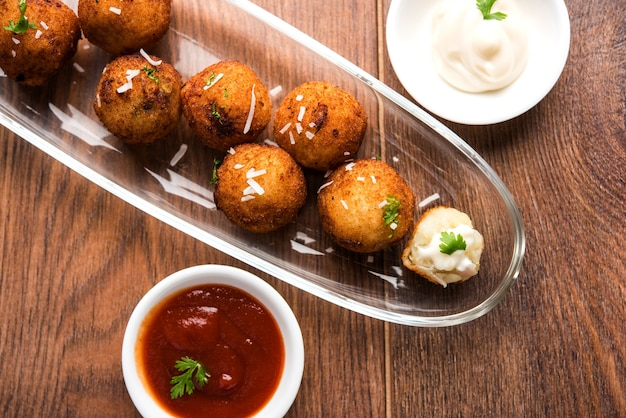 Palline di formaggio di patate fritte o crocchette con ketchup. messa a fuoco selettiva