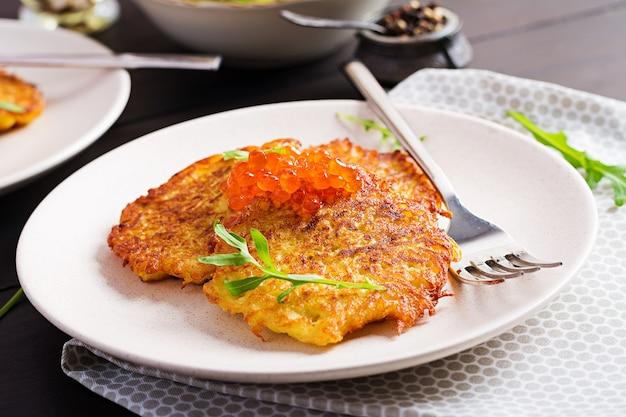 Frittelle di patate fritte con caviale rosso e panna acida, frittella, roesti