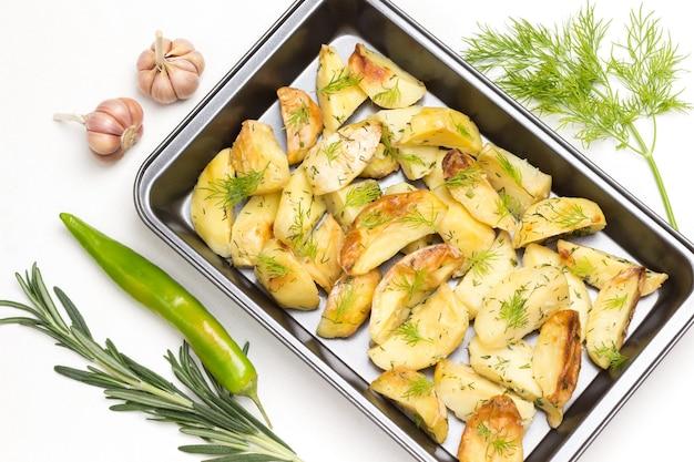 Spicchi di patate fritte con aneto in pallet di metallo alimentare con aglio, baccello di pepe verde e rametto di rosmarino