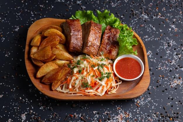 Patate fritte con carne al forno e insalata, sul nero