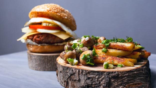 Patate fritte con funghi e un succoso hamburger su tavole di legno della foresta. fast food a casa.