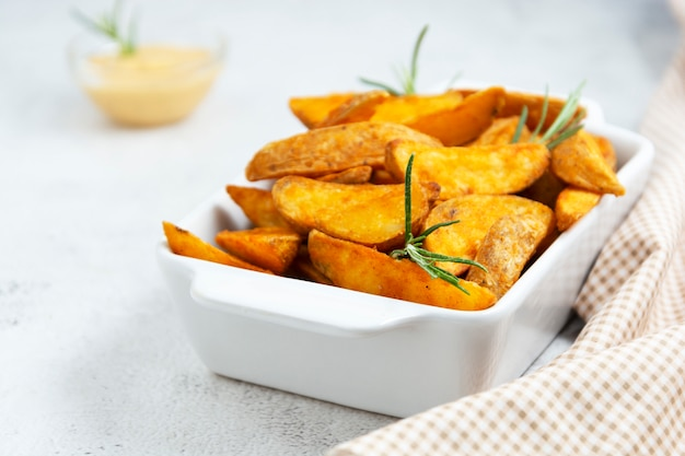 Patate fritte con erbe e salsa. patate arrostite dorate, foto luminosa dell'alimento.