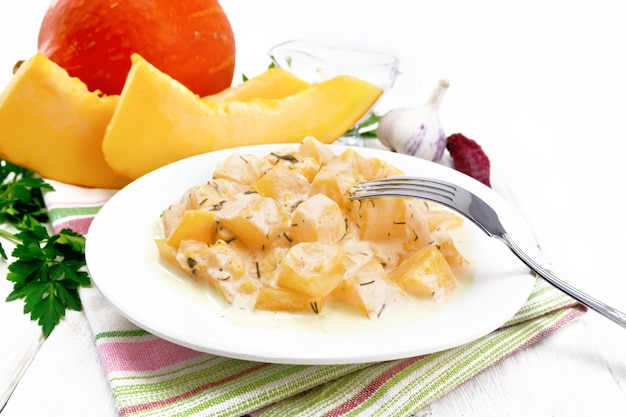 Zucca fritta con aglio, spezie ed erbe aromatiche in salsa di panna acida in un piatto su un asciugamano