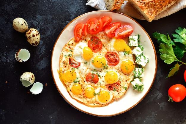 Uova di quaglia fritte in un bellissimo piatto sul tavolo scuro. uova fritte con pomodori e aneto. colazione gustosa e salutare. vista dall'alto