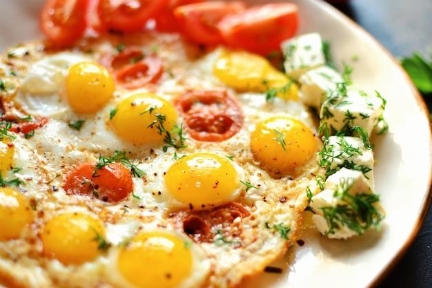 Uova di quaglia fritte in un bellissimo piatto sul tavolo scuro. uova fritte con pomodori e aneto. colazione gustosa e salutare.