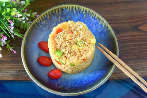 Riso fritto con paprika e zucchine guarnito con pomodorini