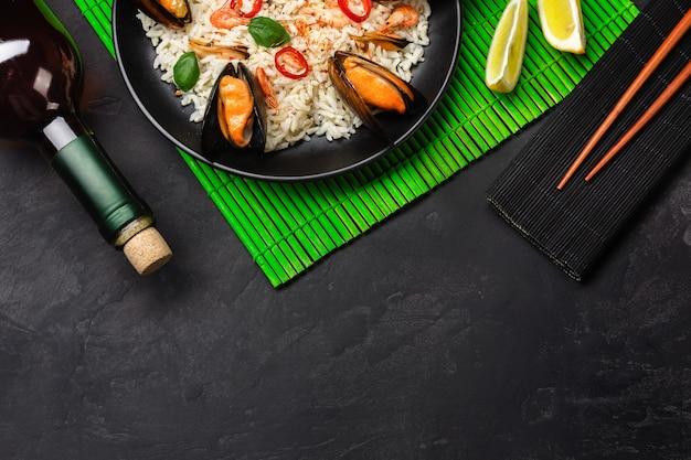 Riso fritto con cozze di mare, gamberi, basilico in un piatto nero con bottiglia di vino, bicchiere di vino, limone, bacchette su stuoia di bambù verde e tavolo in pietra vista dall'alto.