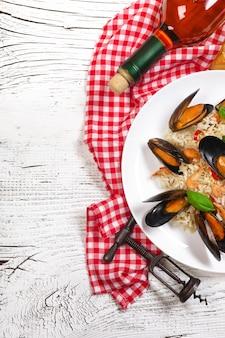 Riso fritto con cozze di mare, gamberi e basilico in un piatto con bottiglia di vino, bicchiere di vino, asciugamano e cavatappi sul tavolo di legno bianco incrinato. vista dall'alto.