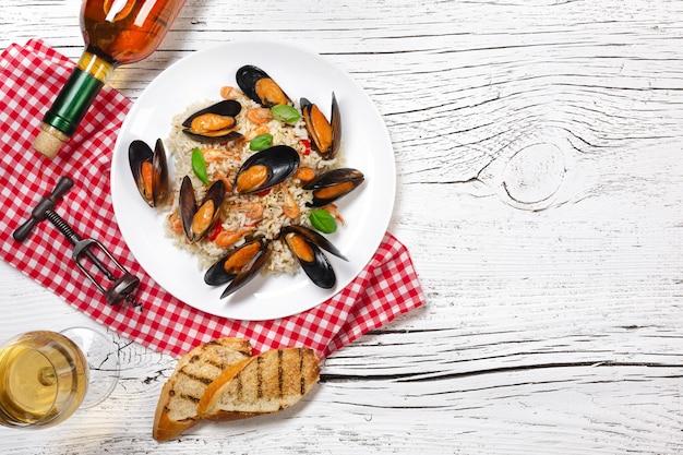 Riso fritto con cozze di mare, gamberi e basilico in un piatto con bottiglia di vino, bicchiere di vino, asciugamano e baguette tostate su tavolo di legno bianco incrinato. vista dall'alto.