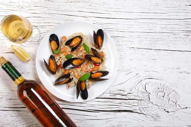 Riso fritto con cozze di mare, gamberi e basilico in un piatto con bottiglia di vino e bicchiere di vino sul tavolo di legno bianco incrinato. vista dall'alto.