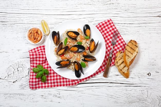 Riso fritto con cozze di mare, gamberi e basilico in un piatto con bicchiere di vino, asciugamano e baguette tostate sul tavolo di legno bianco incrinato. vista dall'alto.