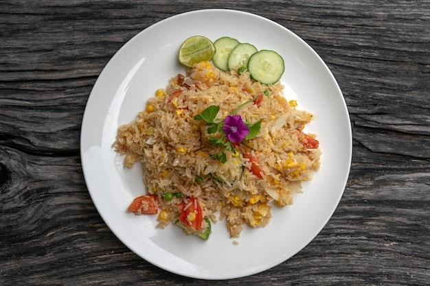 Riso fritto con gamberi e verdure in un piatto bianco su un vecchio tavolo di legno, primo piano. cibo tailandese, cucina tailandese. riso saltato con frutti di mare al ristorante