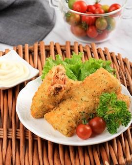 I risol fritti o risol vegetali sono snack indonesiani. servito con salsa maionese. servito con vassoio in bambù, piatto in ceramica con pomodoro