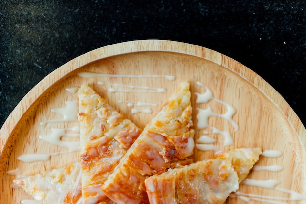 Roti fritti con dessert al latte condensato servito su un piatto di legno.