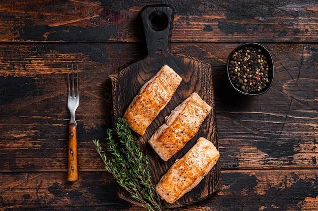 Bistecche di filetto di salmone fritto su una tavola di legno con timo. fondo in legno scuro.