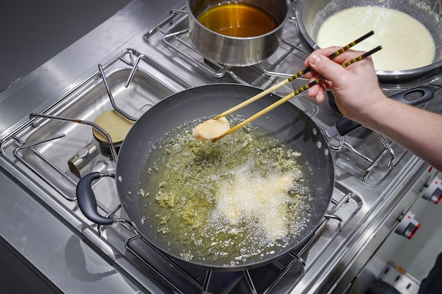 Pezzo di salmone fritto nella coppa dell'olio.