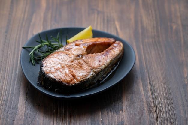 Salmone fritto con limone e rosmarino sul piatto scuro su fondo in ceramica