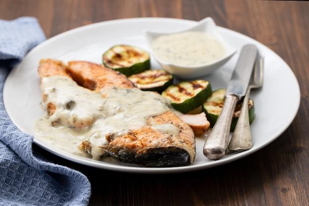 Salmone fritto con salsa e verdure sul piatto bianco su fondo di legno marrone. vista dall'alto.