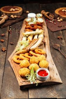 Snack fritti di birra salata sulla tavola di legno con salse