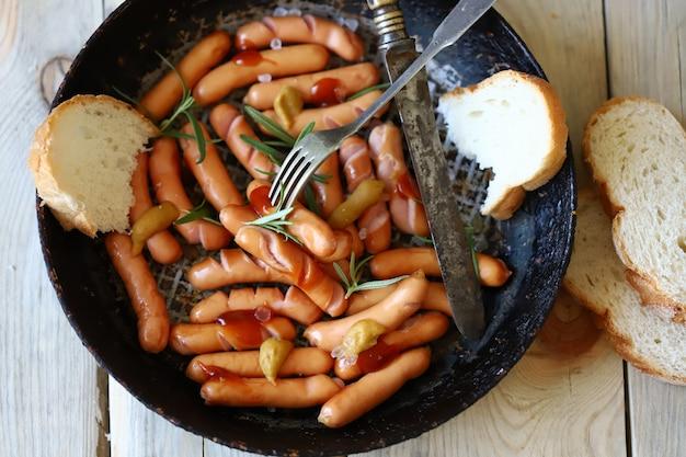 Salsicce fritte con crosta croccante. spuntino alla birra. salsicce tedesche speziate in padella.