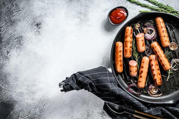 Salsicce fritte con aglio ed erbe aromatiche in padella