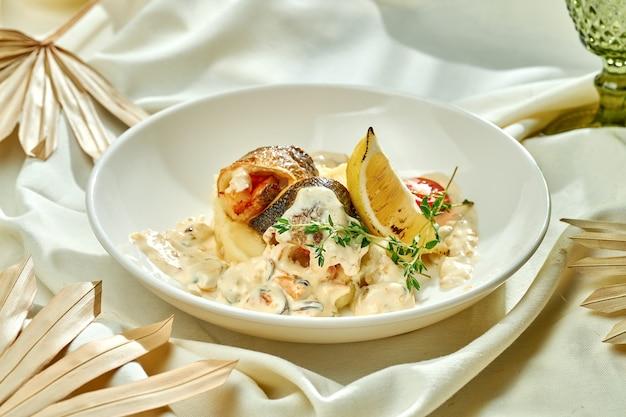 Filetto di branzino fritto con salsa di funghi e purè di patate in un piatto bianco su una tovaglia