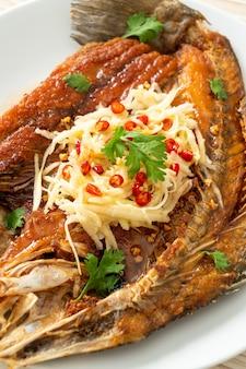Branzino fritto con salsa di pesce e insalata piccante alla piastra