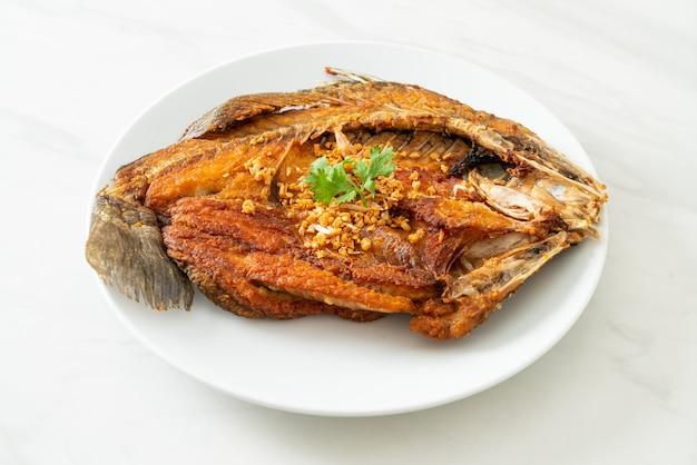 Branzino fritto con aglio su piatto