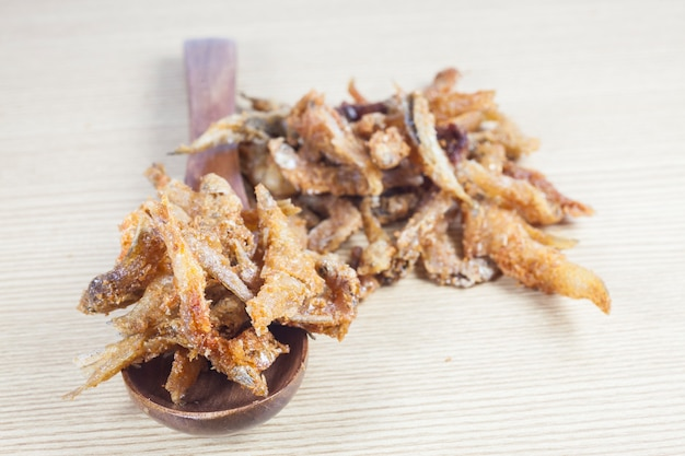Piccoli pesci fritti su fondo di legno