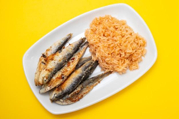Piccole sarde fritte con riso al pomodoro sul piatto bianco su sfondo giallo Foto Premium