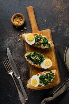 Panini fritti di spinaci, uova e pinoli o bruschette su superficie chiara. deliziosa colazione o spuntino salutare. vista dall'alto.