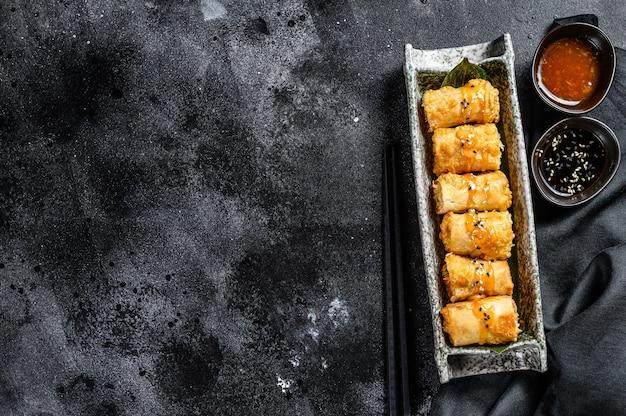 Involtini primavera fritti. sfondo nero. cucina tradizionale cinese