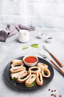 Anelli di calamari fritti con salsa di pomodoro e limone. piastra nera, spazio di copia tavolo in cemento grigio.