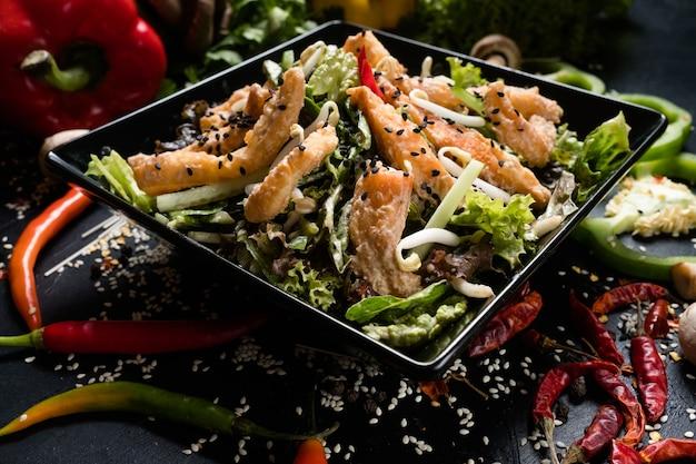 Calamari fritti germogli di grano e insalata di verdure in una ciotola