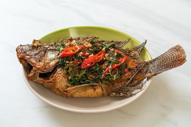 Pesce tilapia fritto con salsa di basilico peperoncino e aglio in cima - stile cibo fatto in casa