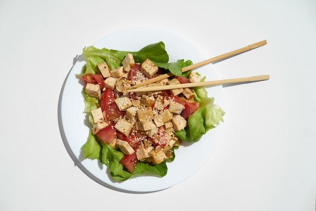 Tofu fritto con verdure e semi di sesamo sul piatto bianco e sfondo di pentecoste, vista dall'alto