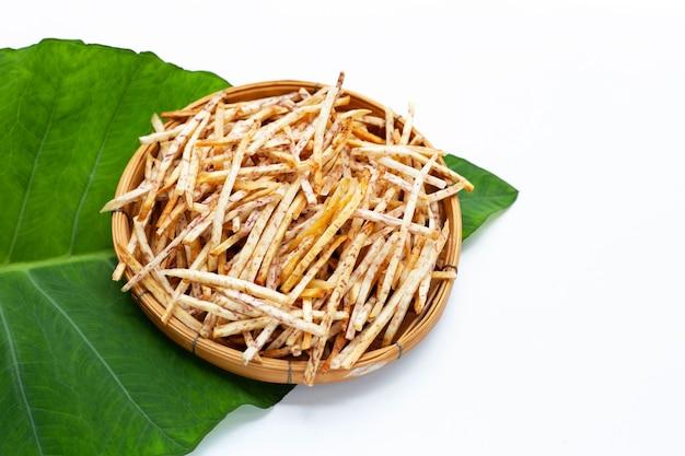 Bastoncini di toro fritti in cesto di bambù su sfondo bianco.