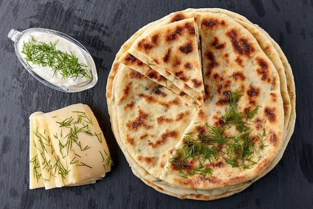 Tortillas fritte con formaggio ed erbe aromatiche e salsa allo yogurt su un piatto bianco su un tavolo di pietra scura