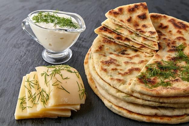 Tortillas fritte con formaggio ed erbe aromatiche e salsa allo yogurt su un piatto bianco