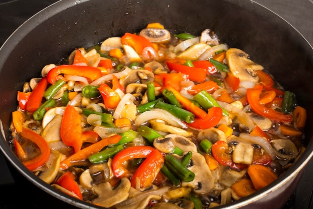 Verdure fritte con funghi in padella su uno sfondo scuro. cucinare il cibo