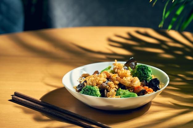 Tagliatelle al wok fritte con frutti di mare, funghi shiitake e verdure in salsa agrodolce. cucina cinese.