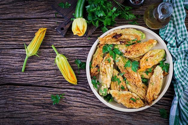 Fiori di zucca fritti ripieni di ricotta ed erbe verdi. cibo vegano. cucina italiana. vista dall'alto