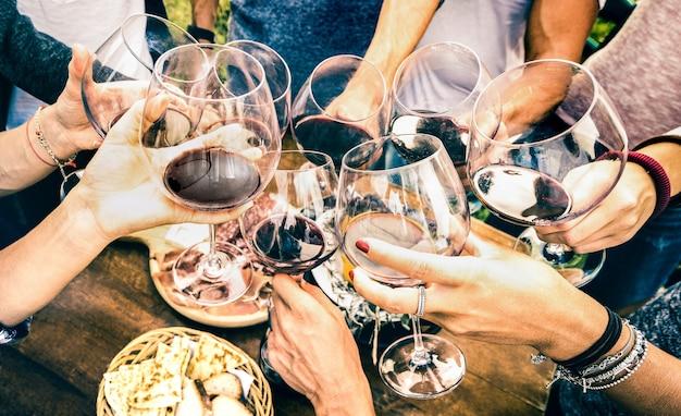 Le mani di un amico brindano con vino rosso mentre si divertono fuori a fare il tifo con una degustazione di vini