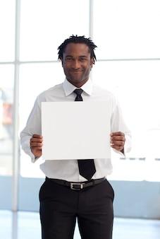 Uomo d'affari afroamericano amichevole che tiene una carta bianca